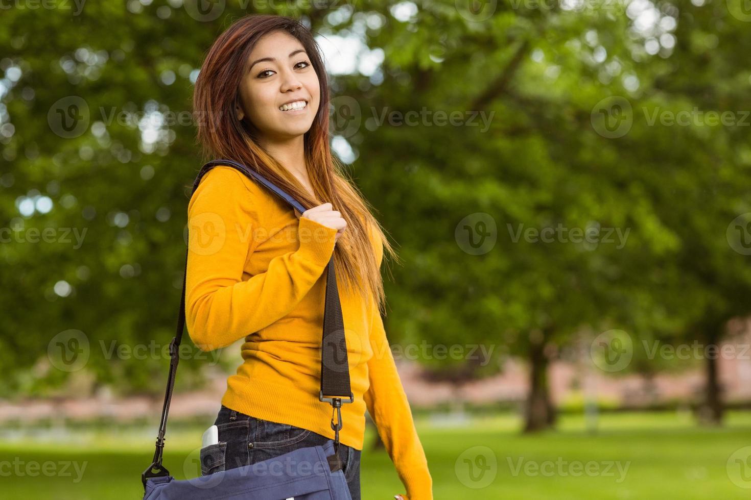 estudante feminino com bolsa no parque foto