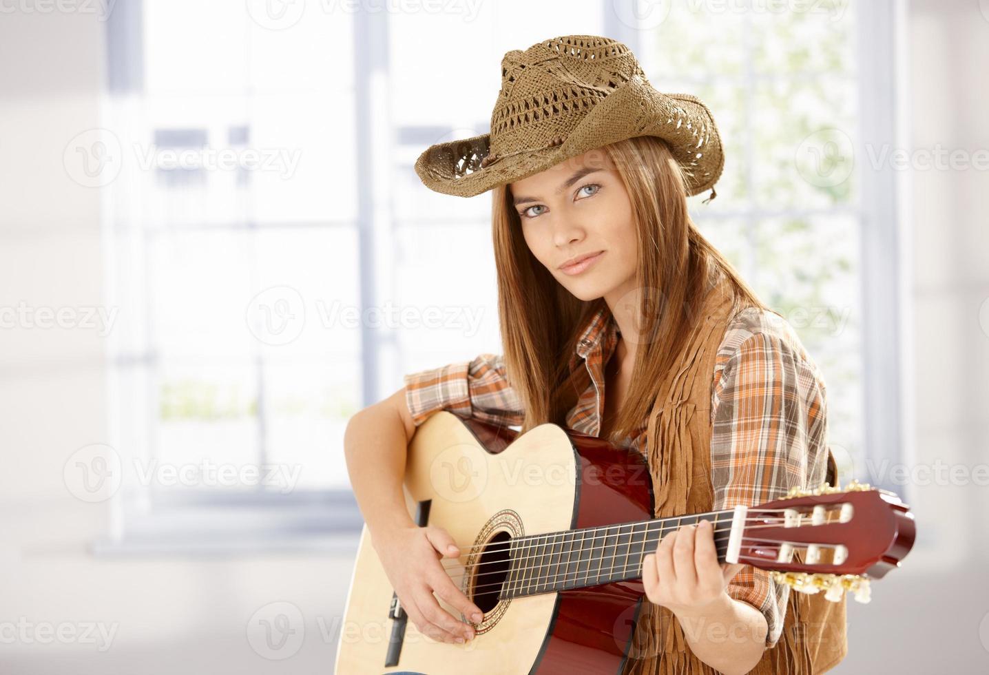 jovem fêmea tocando violão em estilo ocidental foto