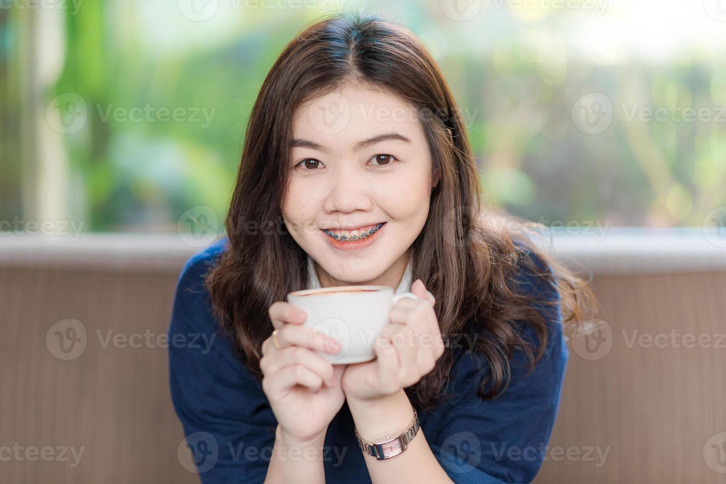 heureux asiatique souriant étudiante boire du café photo
