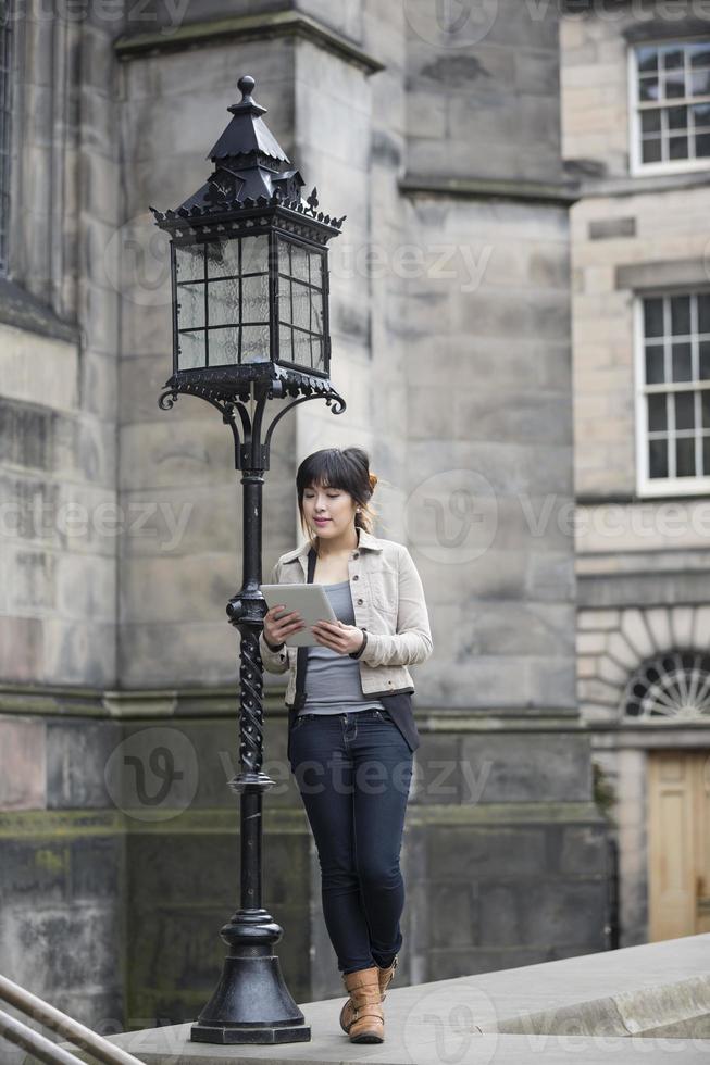mujer asiática viajero de la ciudad con tableta digital foto