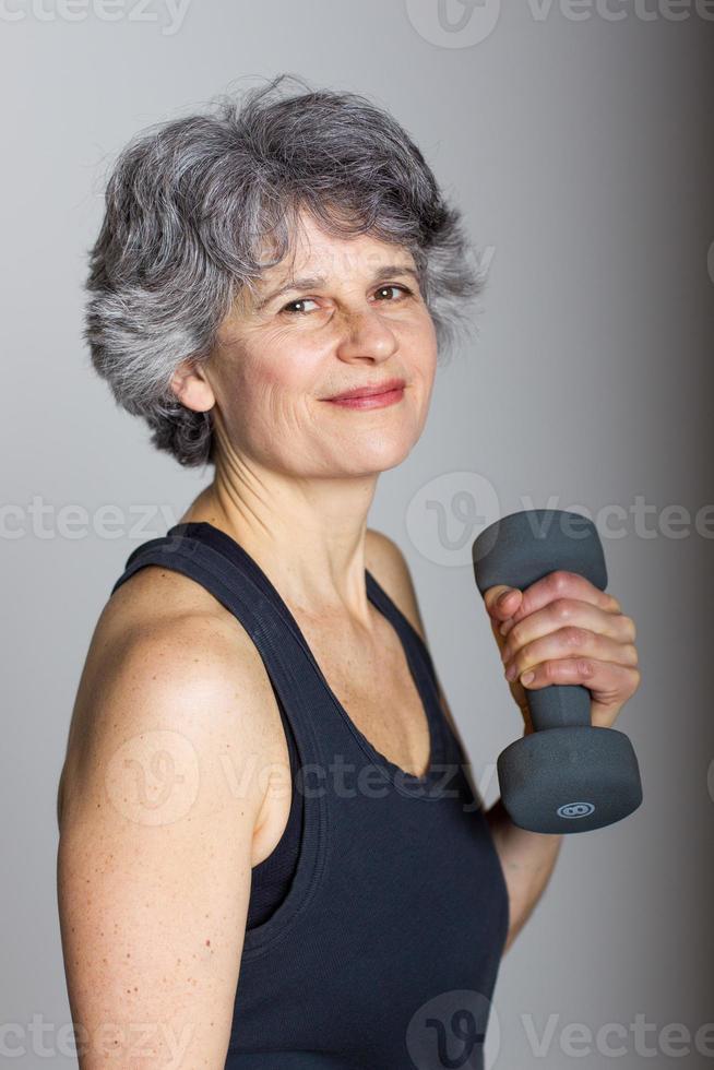 treinador de esportes feminino de meia idade com haltere foto