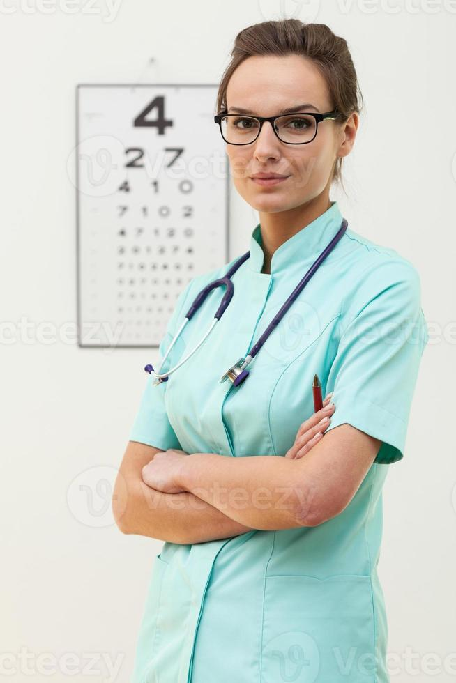 Confident female optometrist standing with arms crossed photo