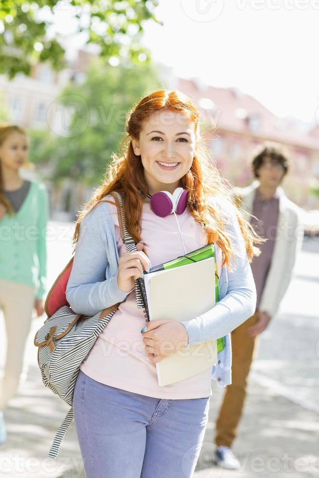 Portrait of young female student with friends photo