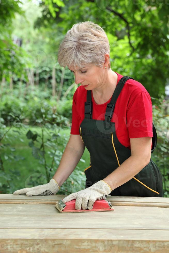 trabajadora que restaura la puerta de madera vieja foto