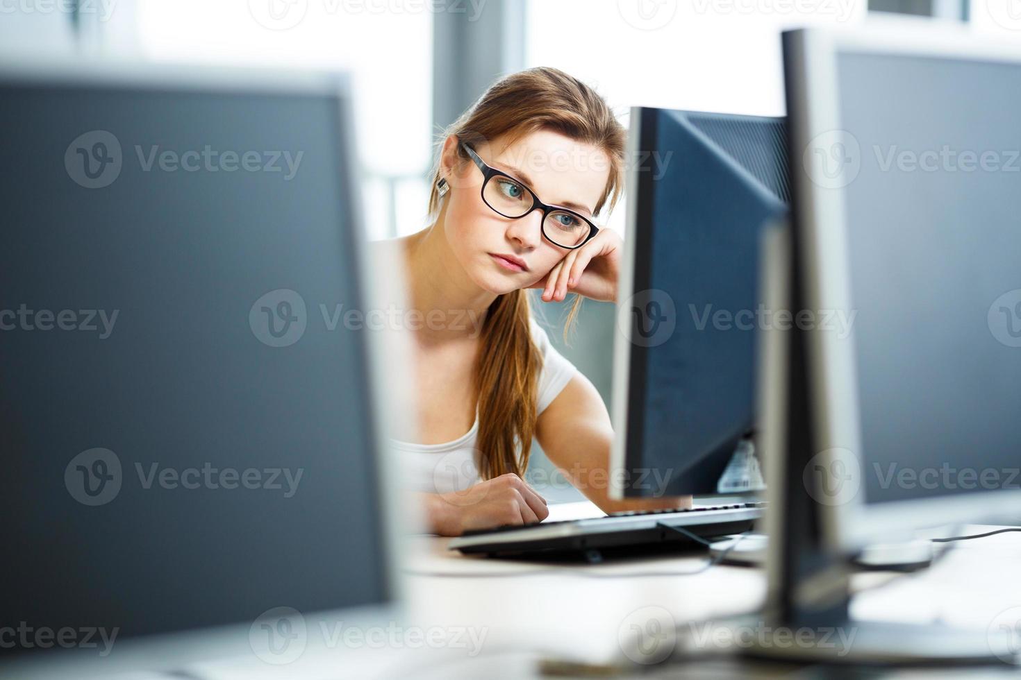 Pretty, female college student in a library photo