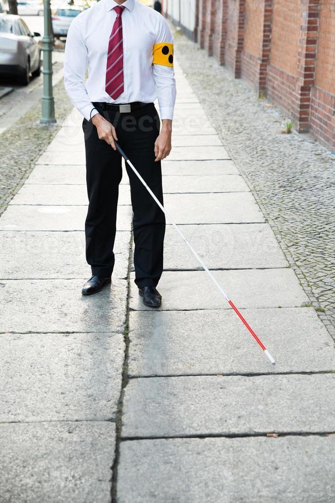 Blind Man Walking On Sidewalk photo