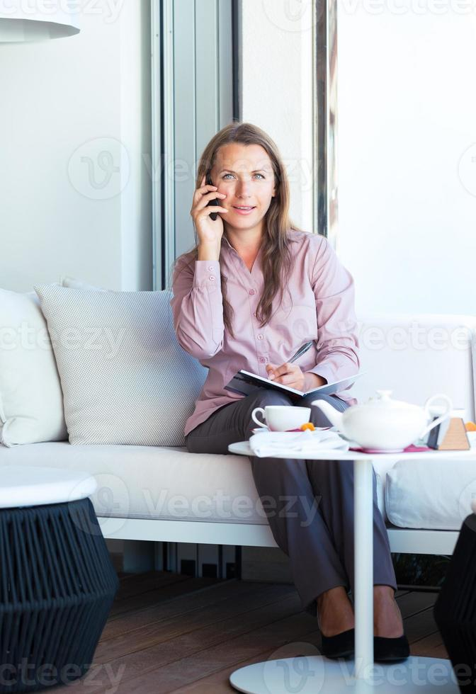 Businesswoman talking on the phone in a cafe photo