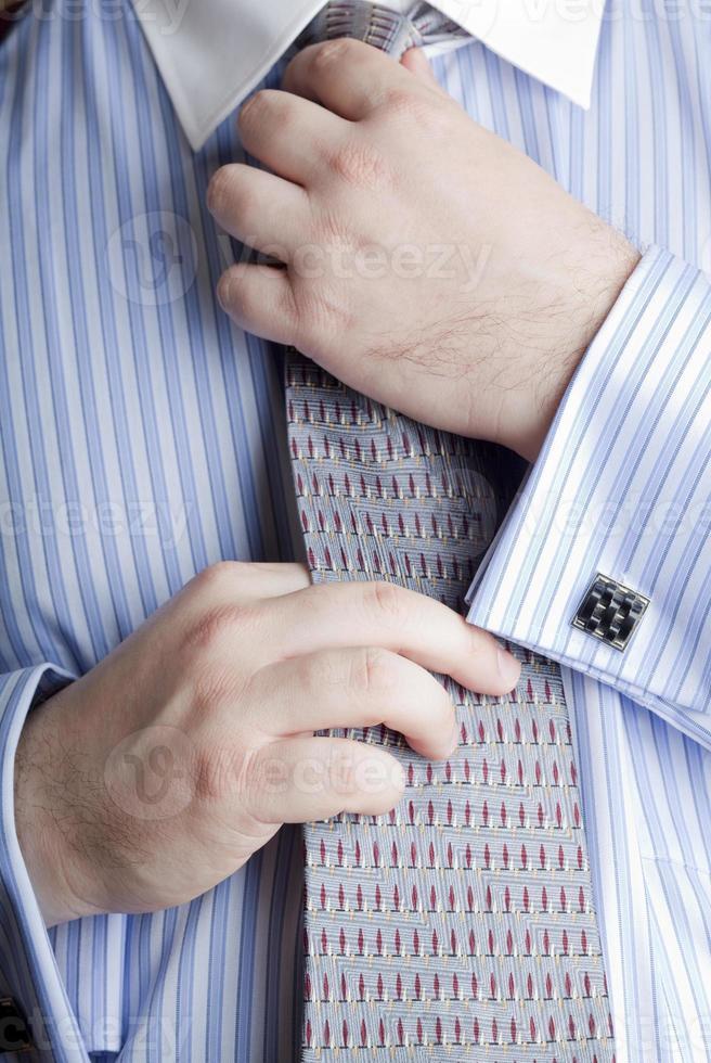 Businessman straightening his tie photo