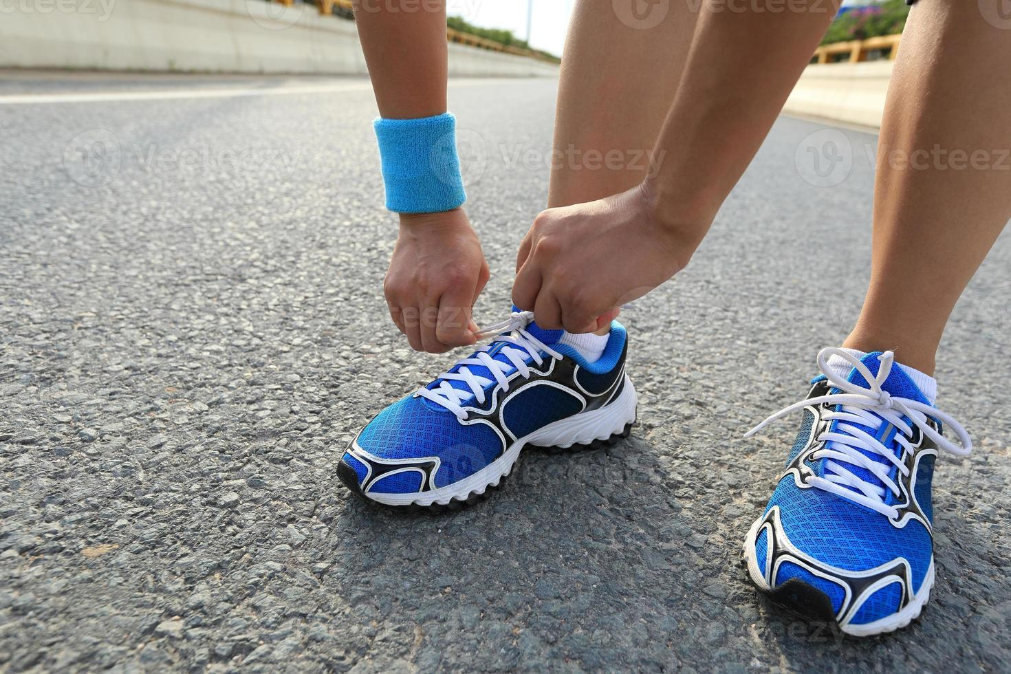 young woman runner tying shoelaces on city road photo