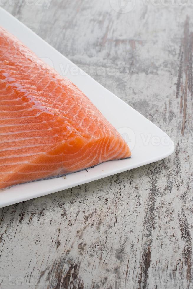 Deliciosa porción de filete de salmón fresco sobre fondo vintage de madera foto