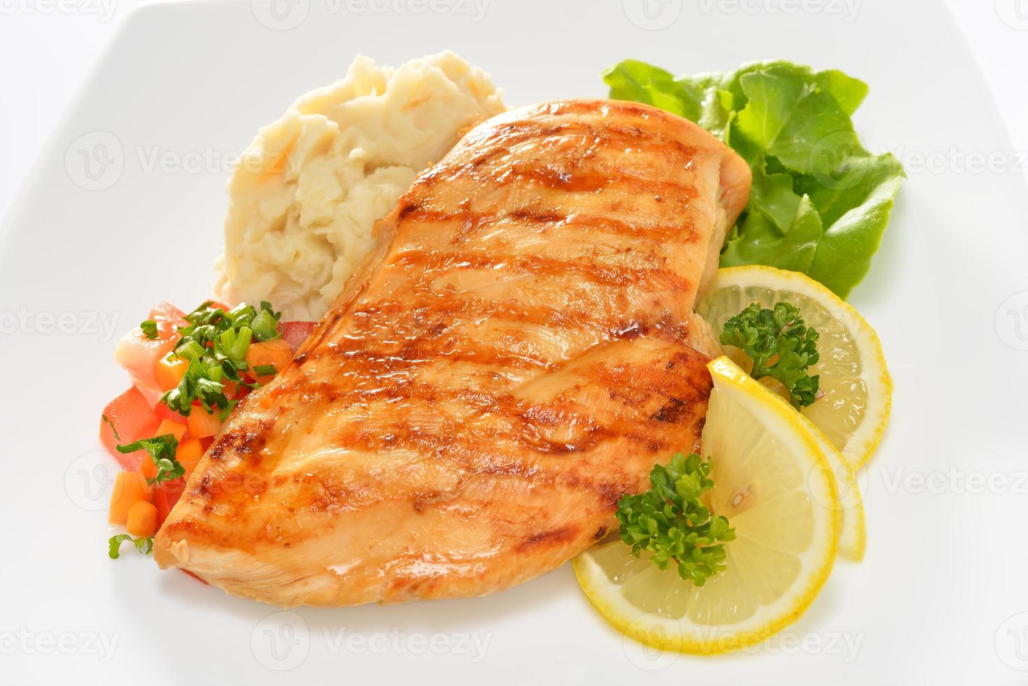 Grilled chicken on plate with mashed potatoes and lemon photo