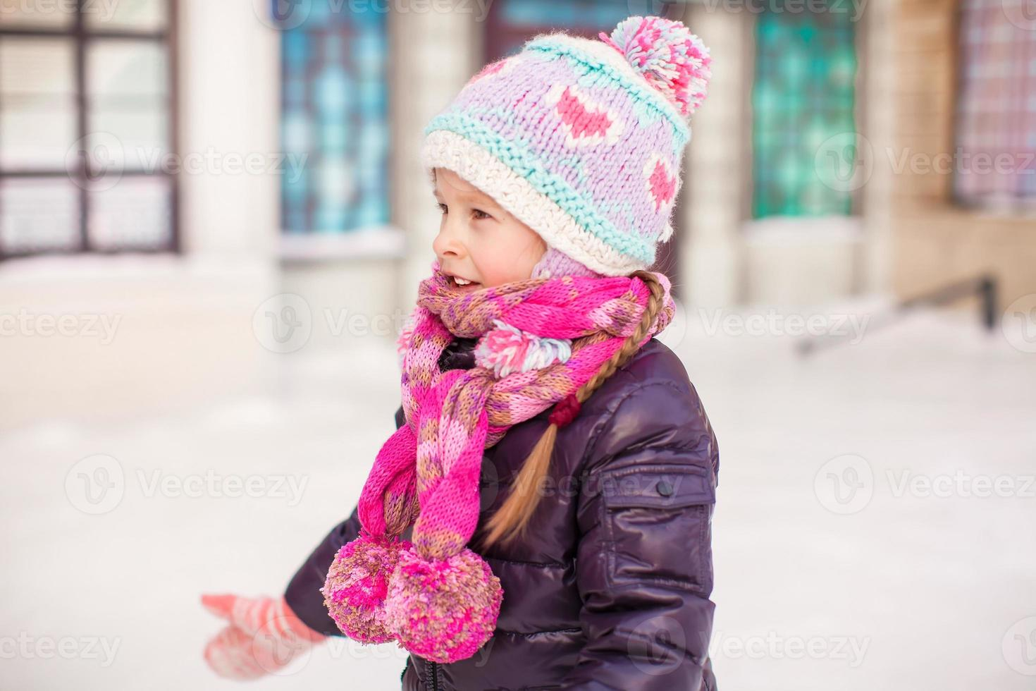 Adorable little happy girl skating on the ice-rink photo