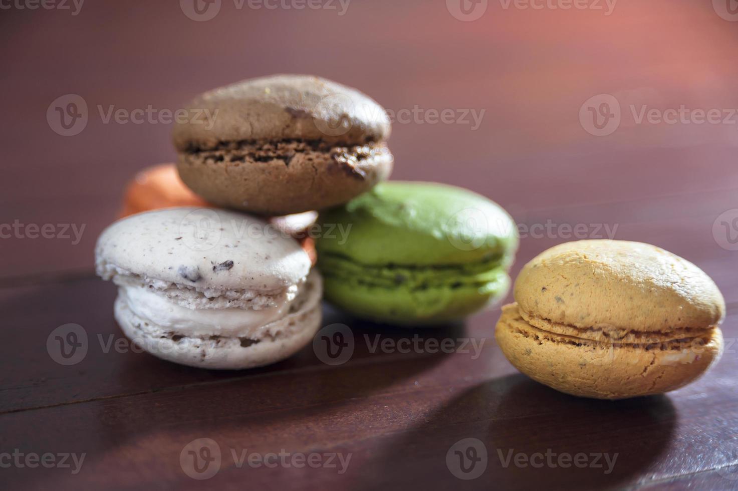 Coloridos macarons franceses en un piso de madera, merienda foto