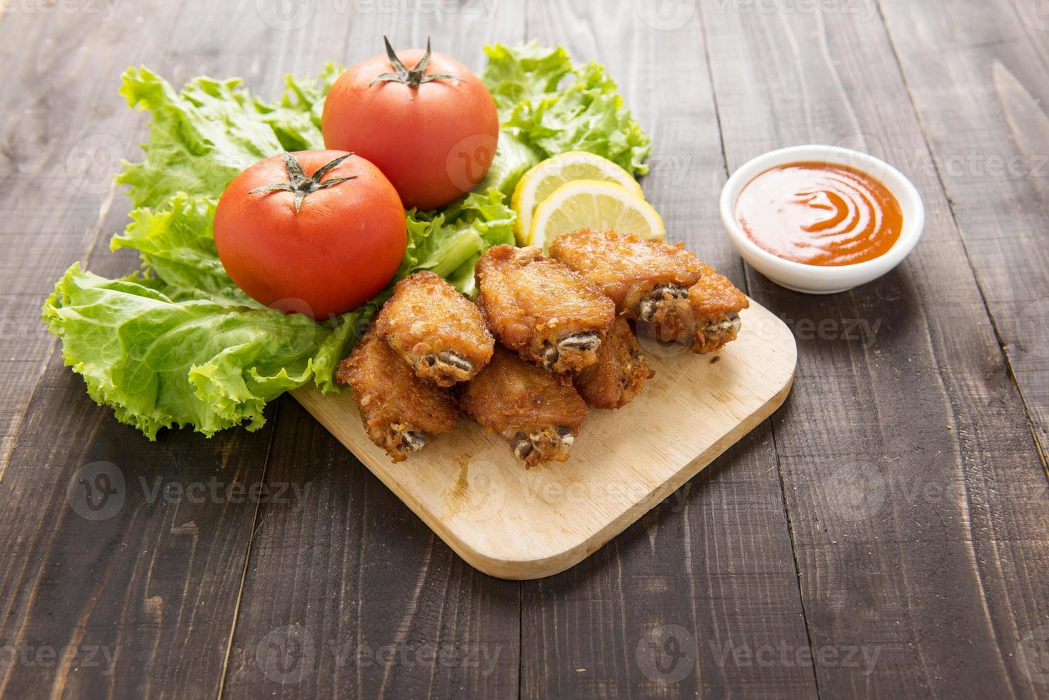 Fried chicken wings on wooden background photo