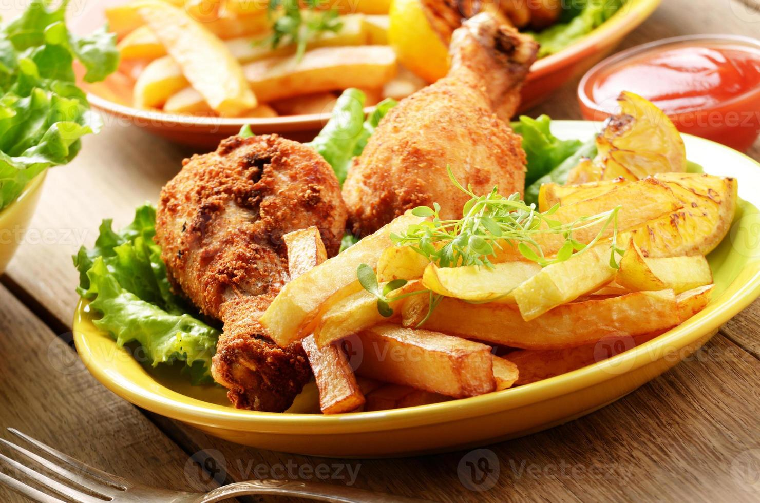 Fried drumsticks with french fries photo