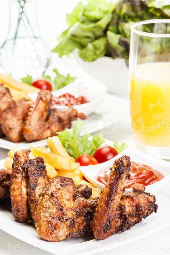 alitas de pollo con papas fritas y salsa picante foto