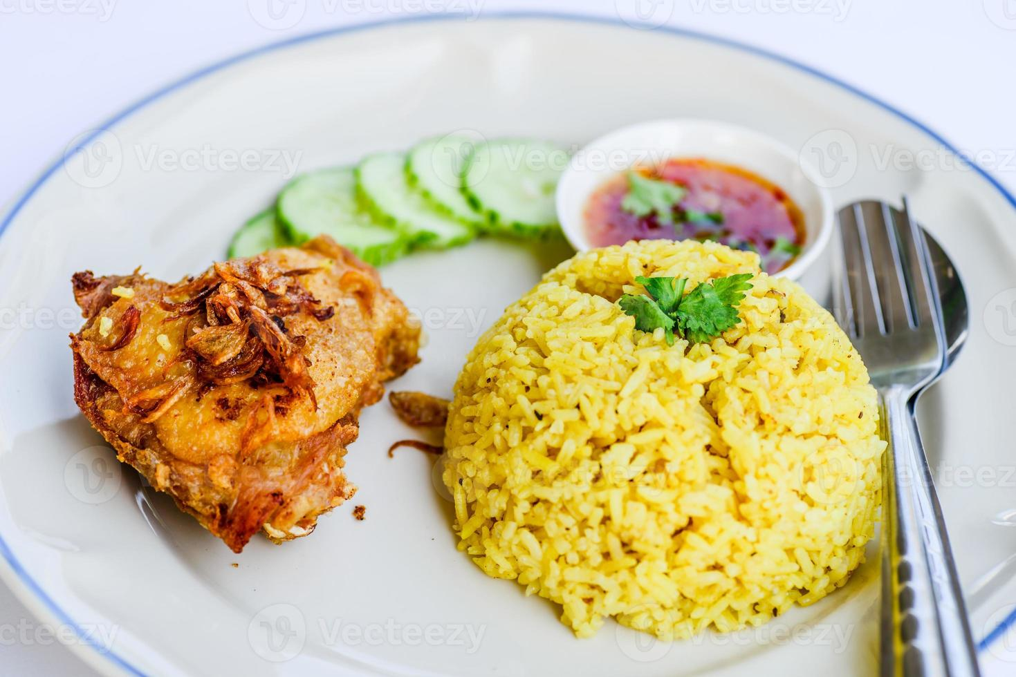 Yellow rice with fried chicken on dish. photo
