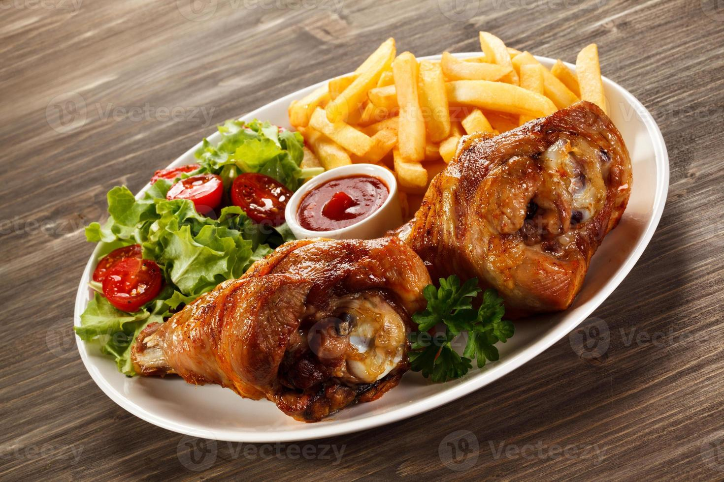 Roasted chicken drumsticks, French fries and vegetables photo