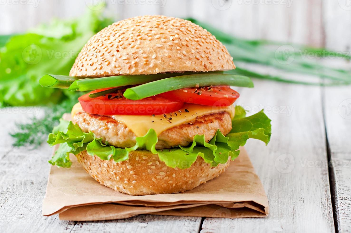 Sandwich with chicken burger, tomatoes, cheese and lettuce photo
