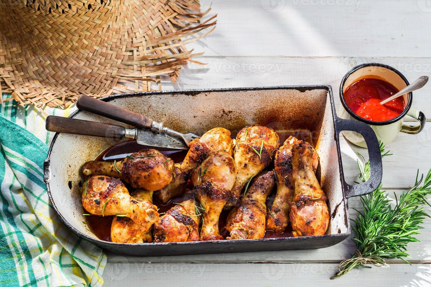 Hot chicken legs with herbs and sauce in rustic kitchen photo