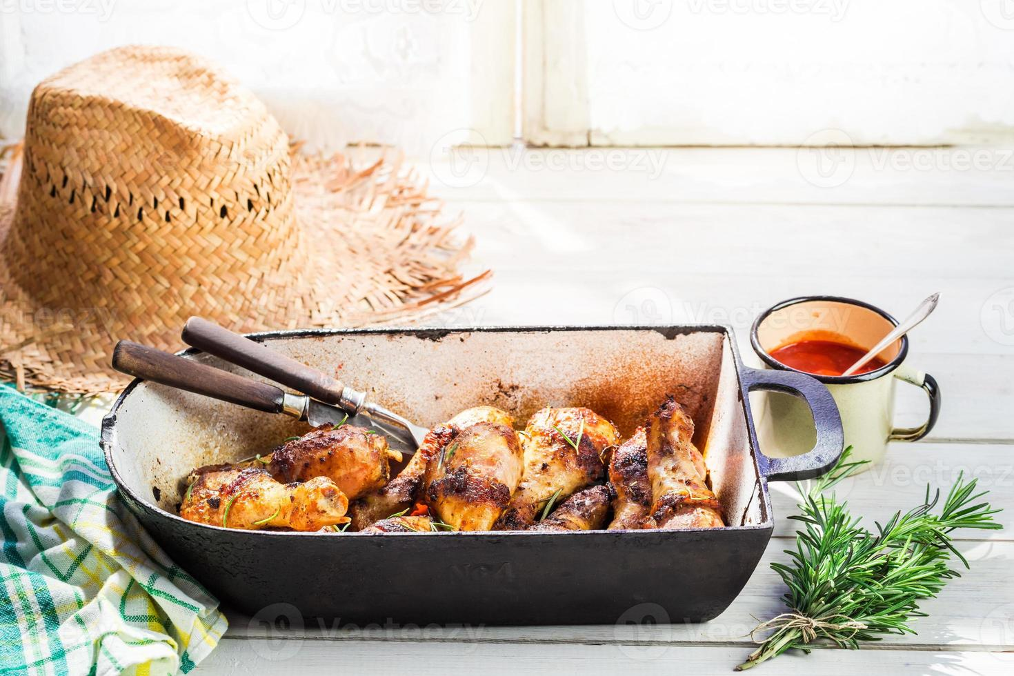 Hot chicken legs with herbs and sauce in summer kitchen photo