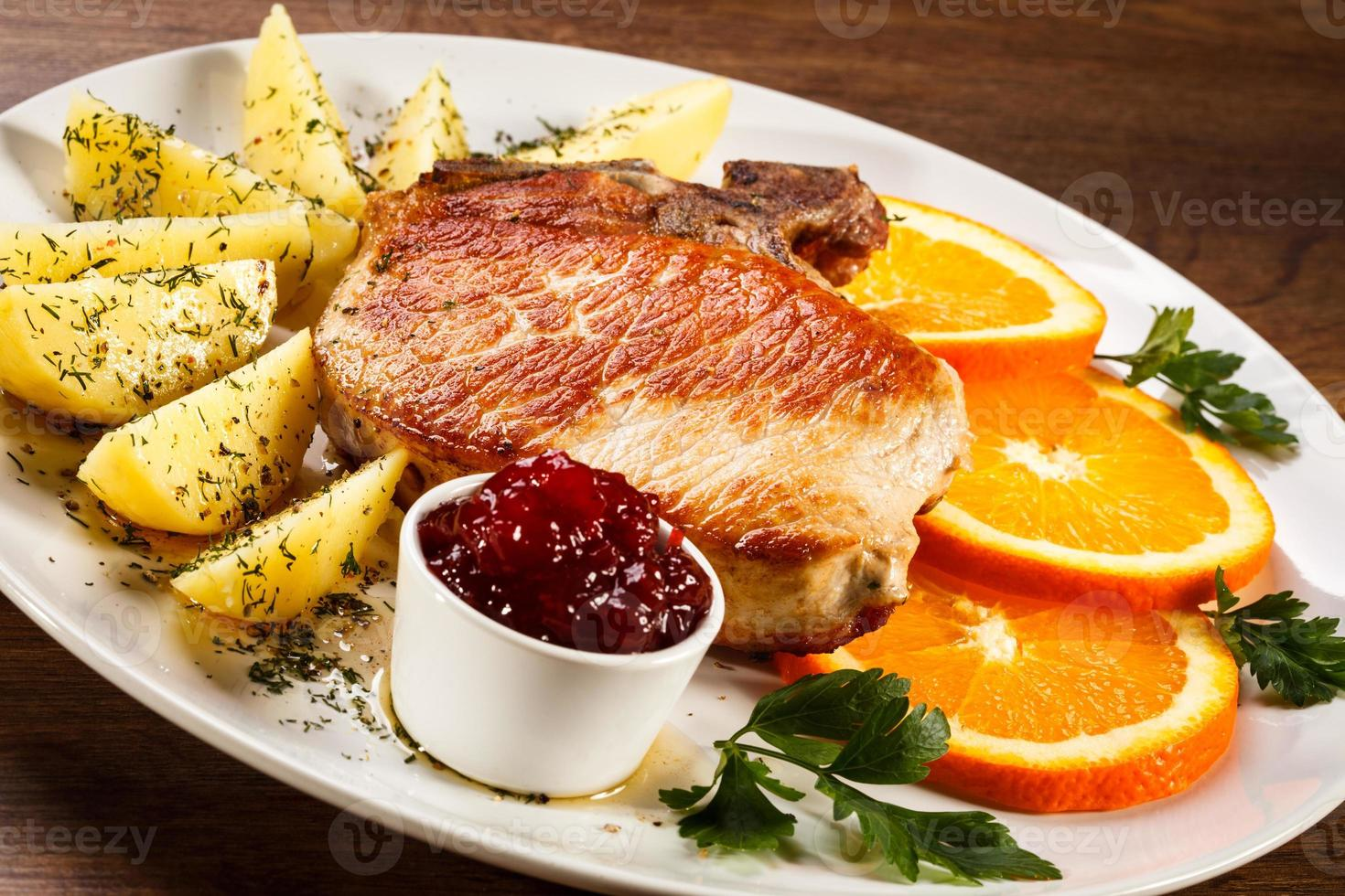 Pork chop, boiled potatoes and vegetables photo
