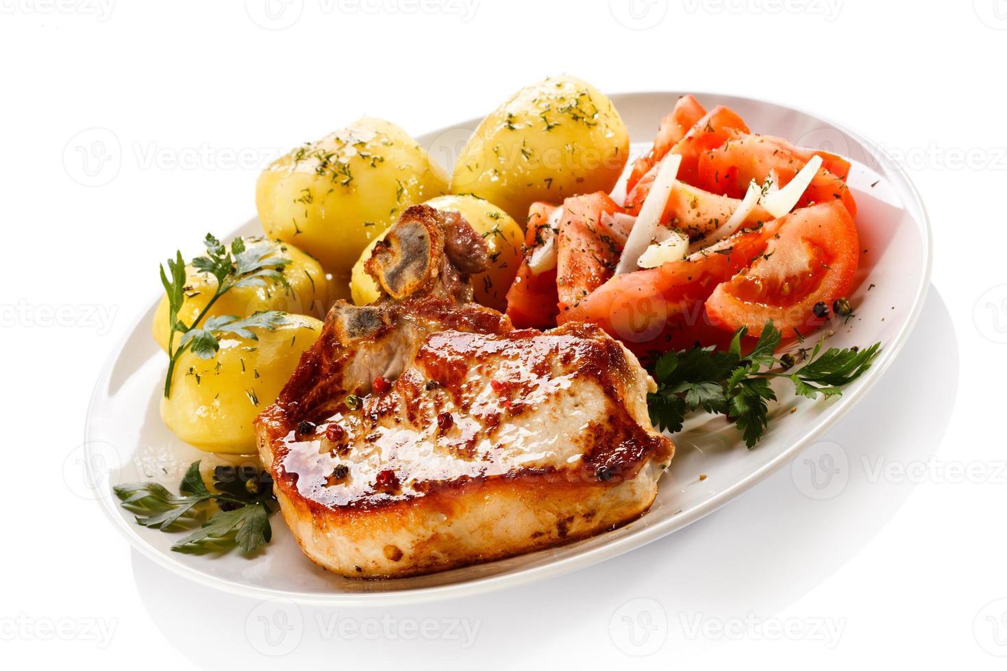 Chuleta de cerdo, patatas hervidas y verduras sobre fondo blanco. foto