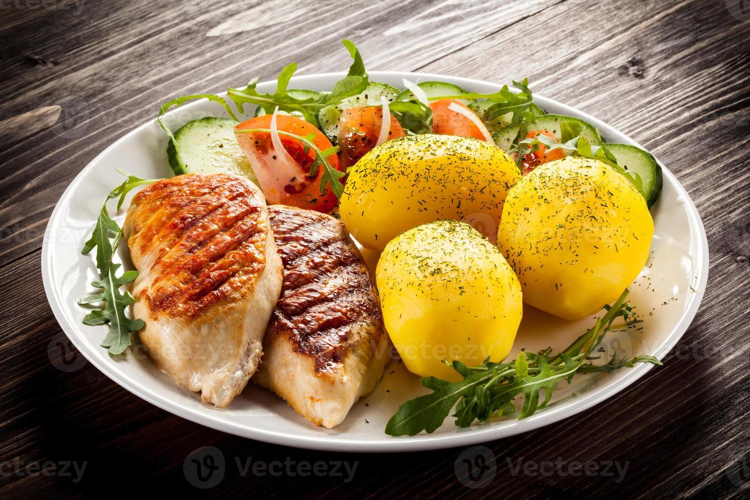 Grilled chicken fillets, boiled potatoes and vegetables photo