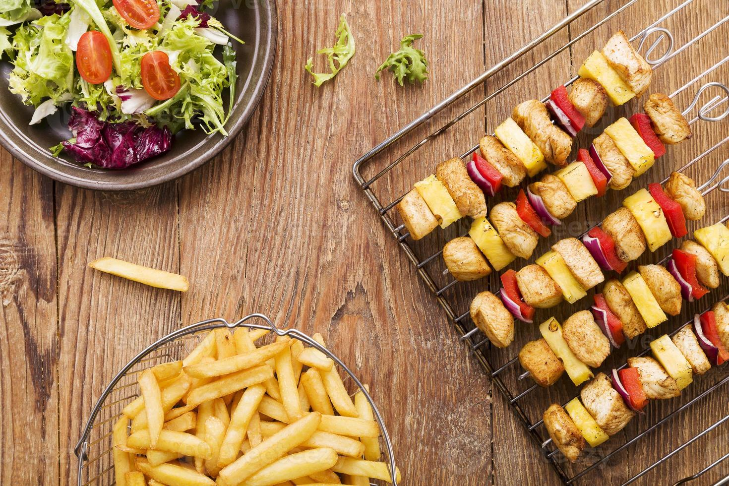 Grilled chicken skewers with pineapple, peppers and onions serve photo