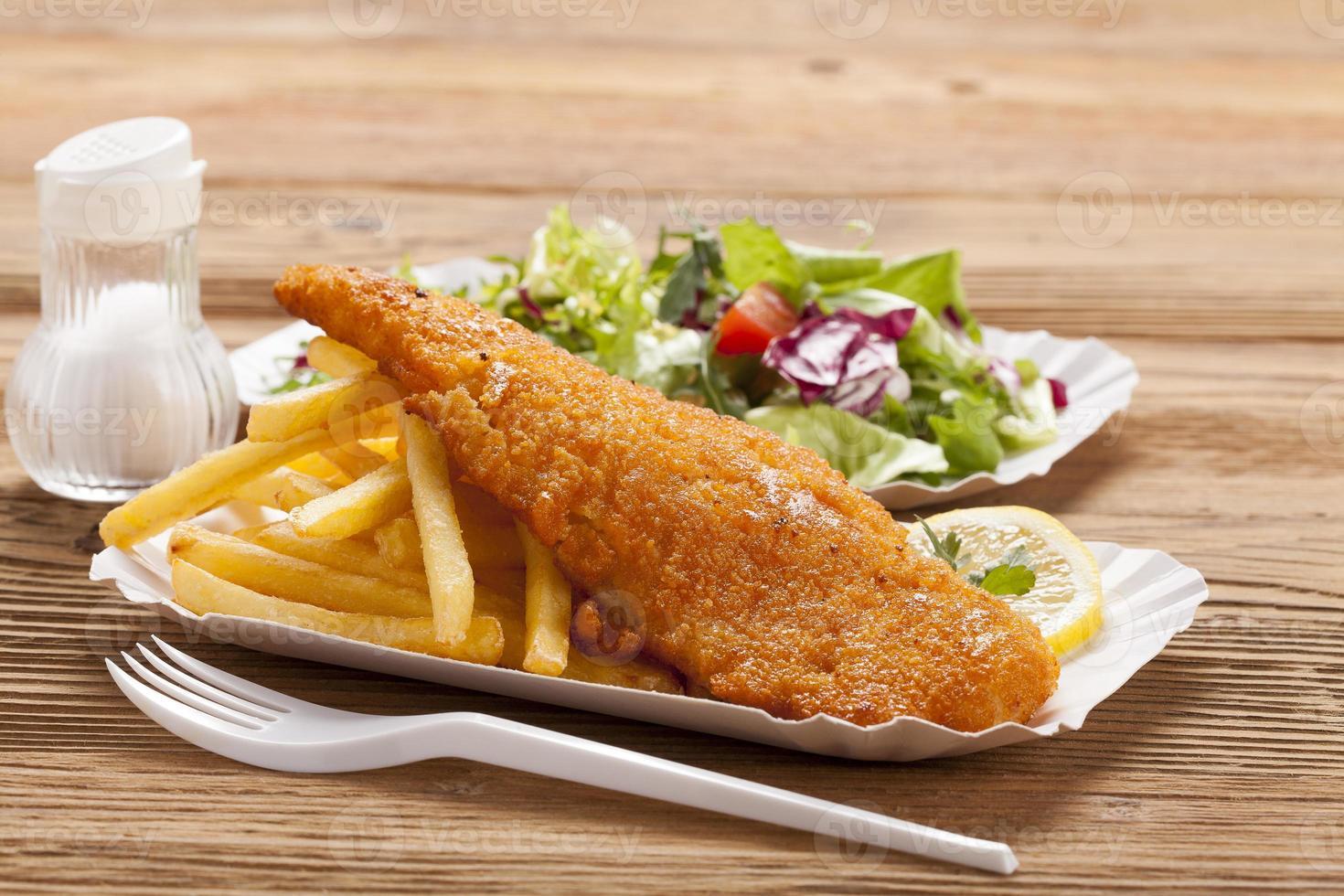 pescado frito con patatas fritas en una bandeja de papel foto