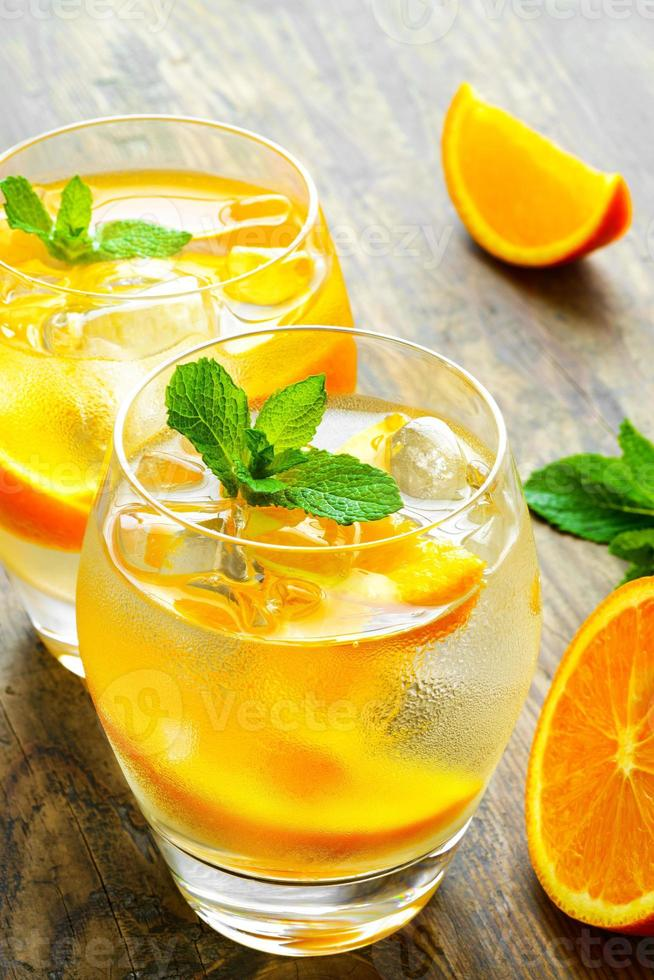 Cold drinks with ice and mint. Orange cocktail on rustic photo