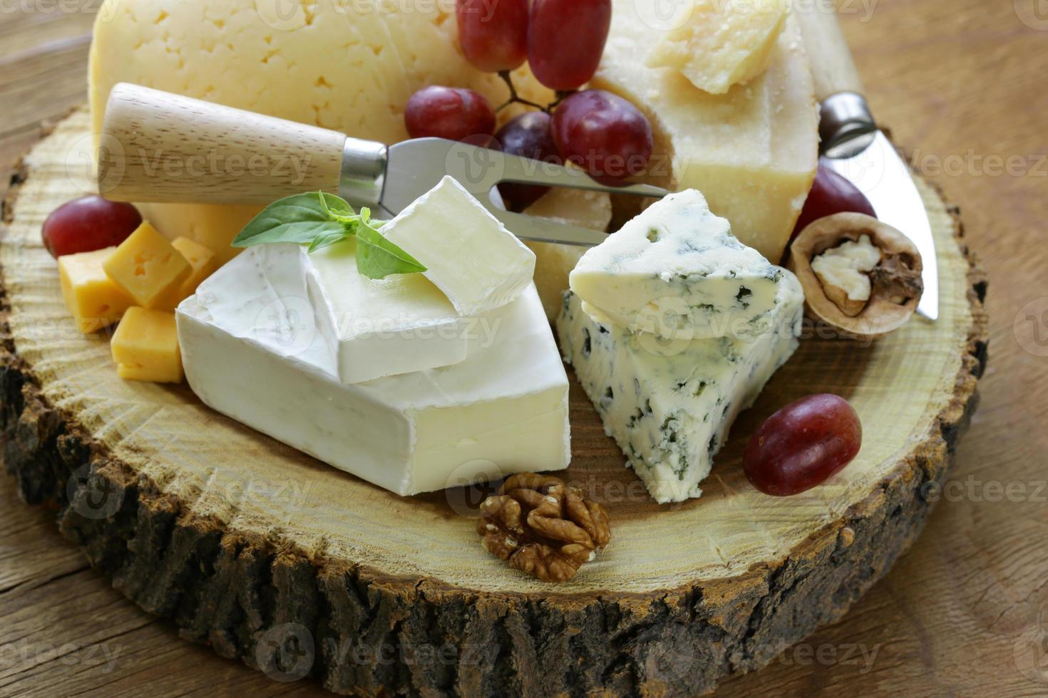 cheeseboard with assorted cheeses (parmesan, brie, blue, cheddar) photo