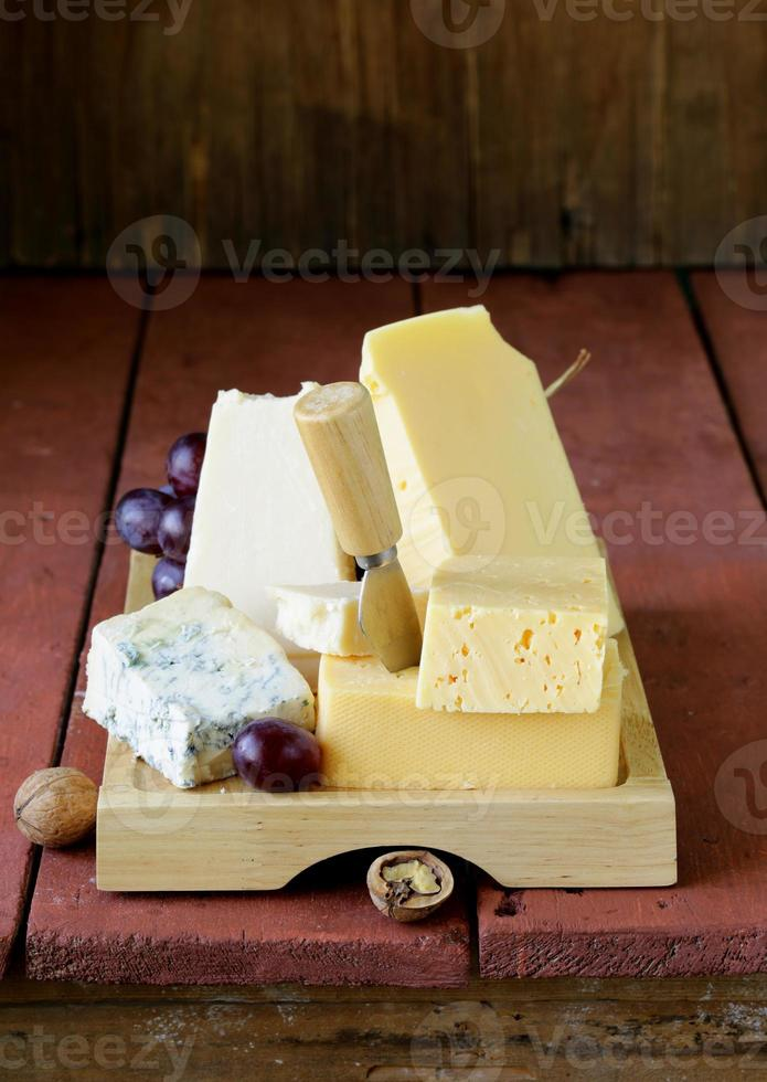 Cheese assortment served on a wooden board with grapes photo