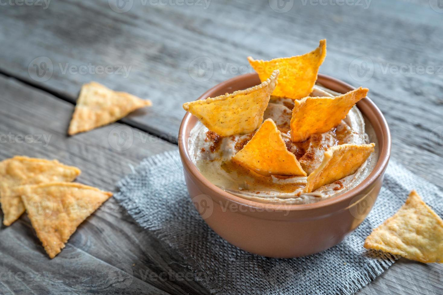 Bowl of hummus with corn chips photo