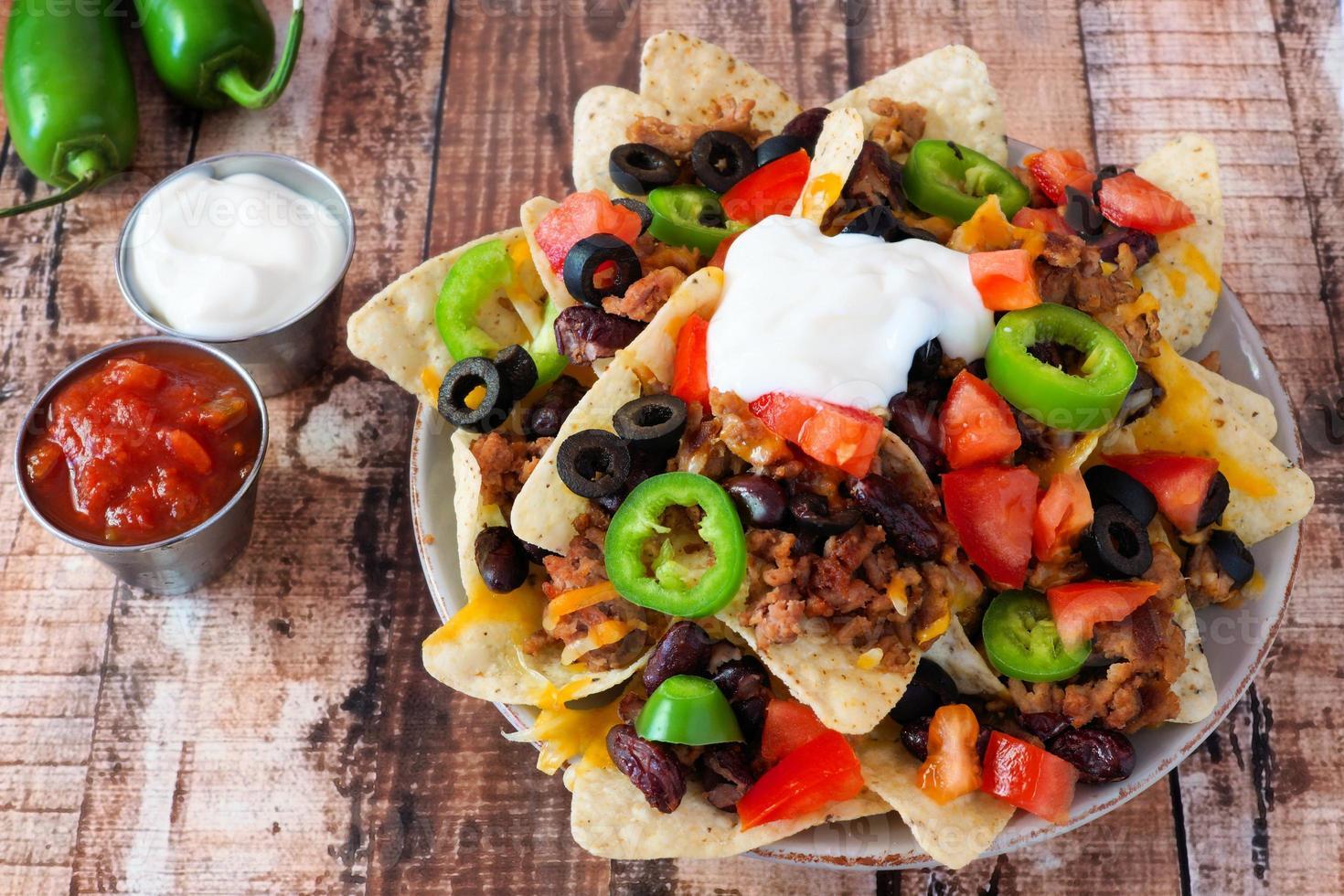 Nacho chips mexicanos totalmente cargados sobre fondo de madera rústica foto