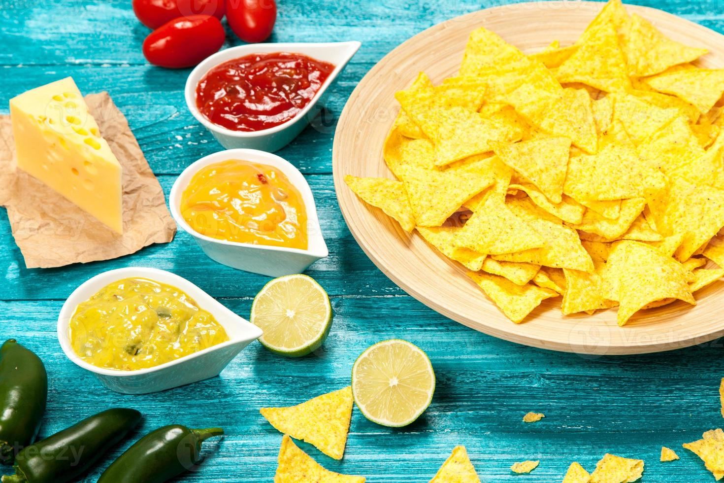 Plate of nachos with different dips photo