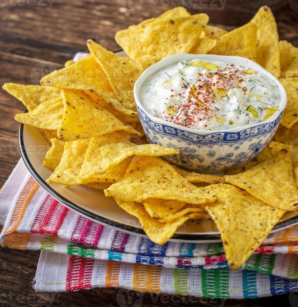 chips de tortilla y salsa de crema con hierbas frescas, ajo foto