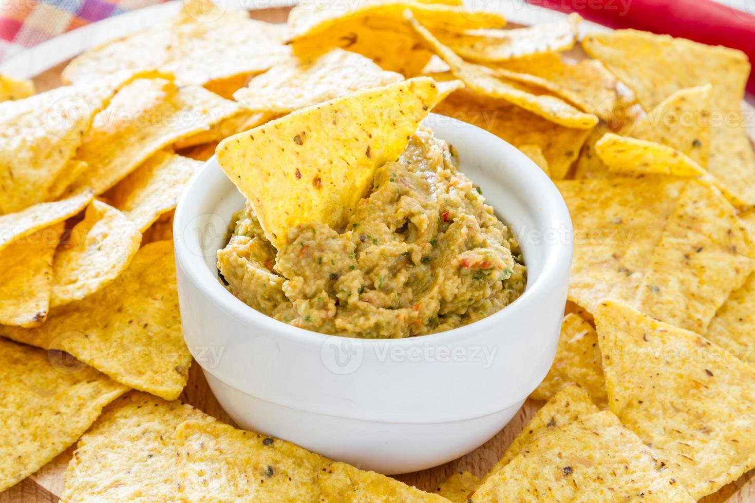Guacamole sauce in white bowl, nacho chips on wood board photo