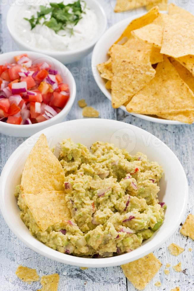 spicy avocado sauce and assorted sauces with corn chips photo