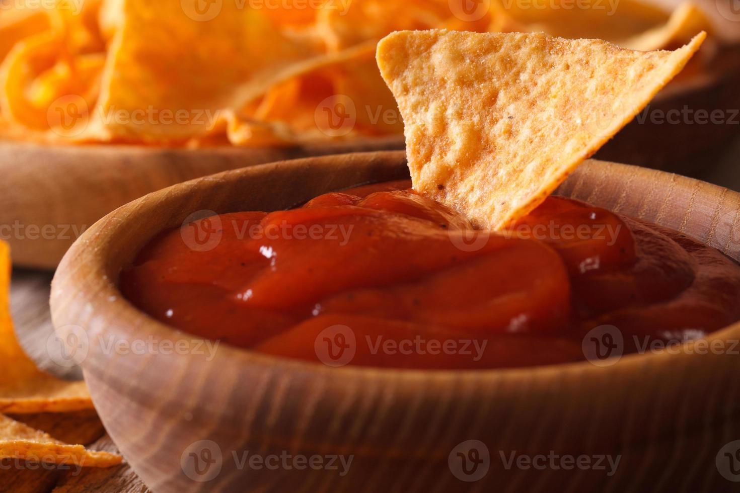 salsa de tomate y chips de maíz nachos macro. horizontal foto