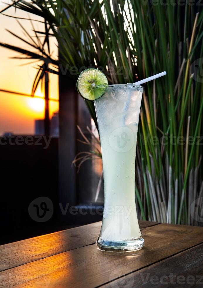 delicioso jugo de limón en vaso con sol. foto