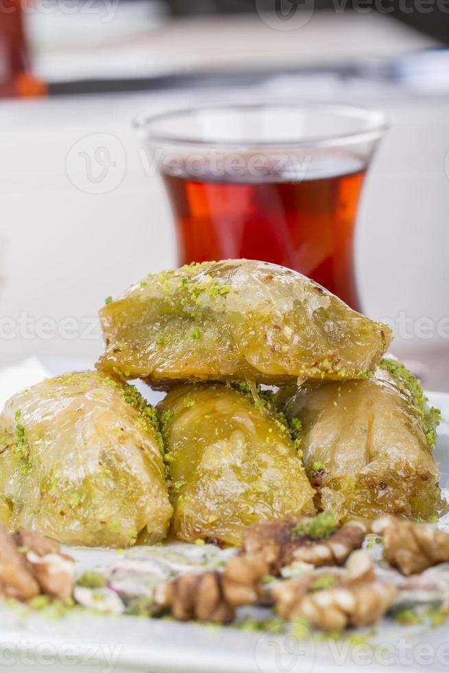 baklava de postre árabe turco con té, miel y nueces foto