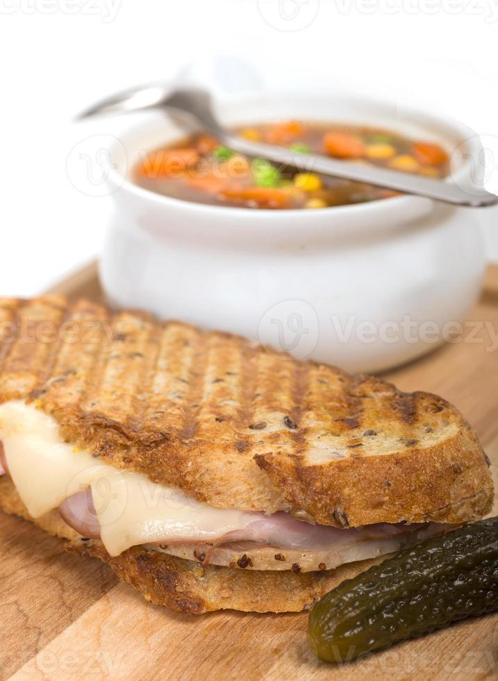 Delicious ham, pork and swiss cheese panini with vegetable soup photo