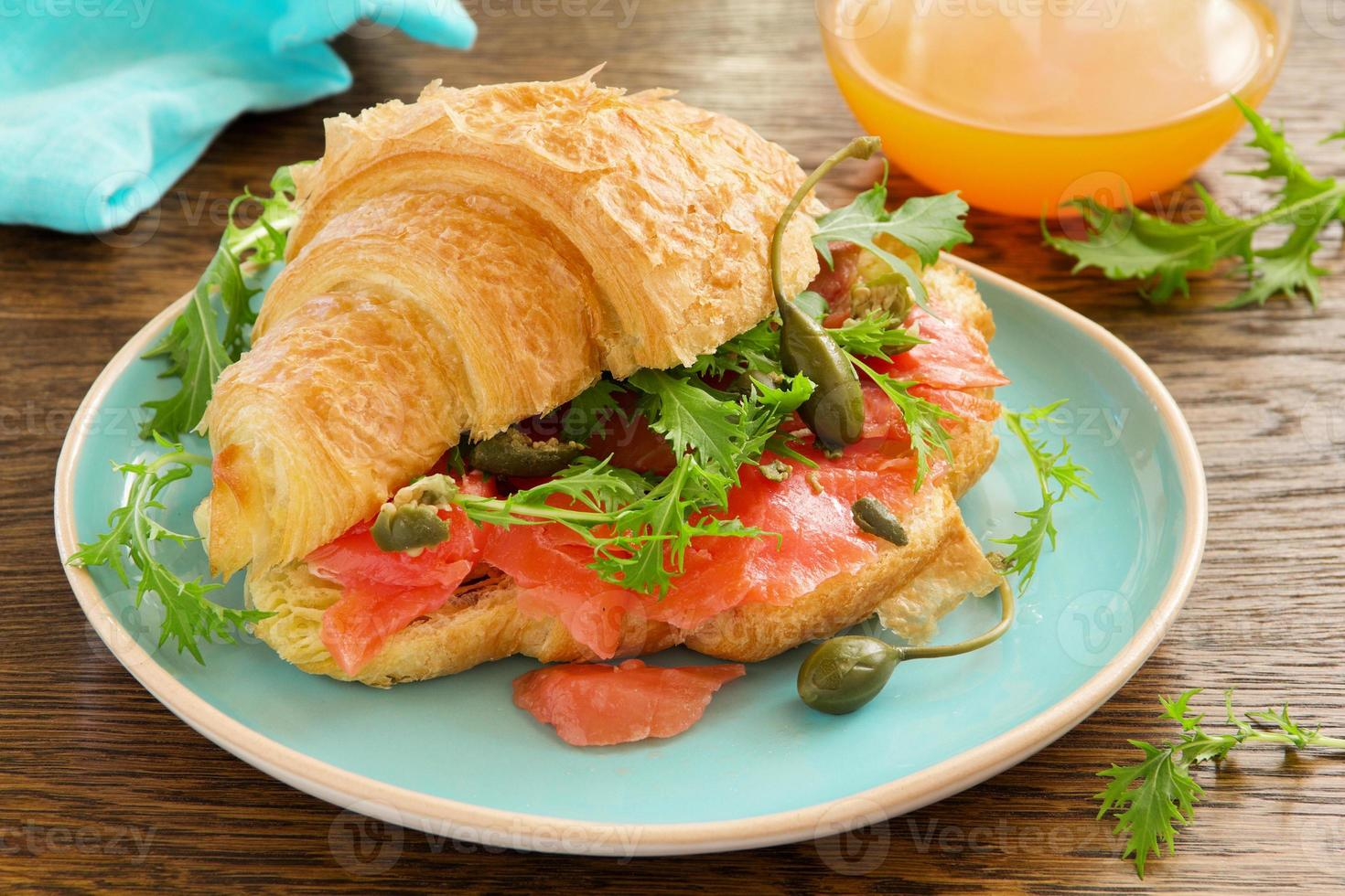Croissant with salmon and capers. photo