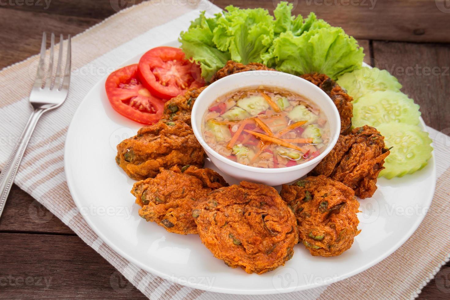Pastel de pescado frito y verduras en el plato, comida tailandesa foto