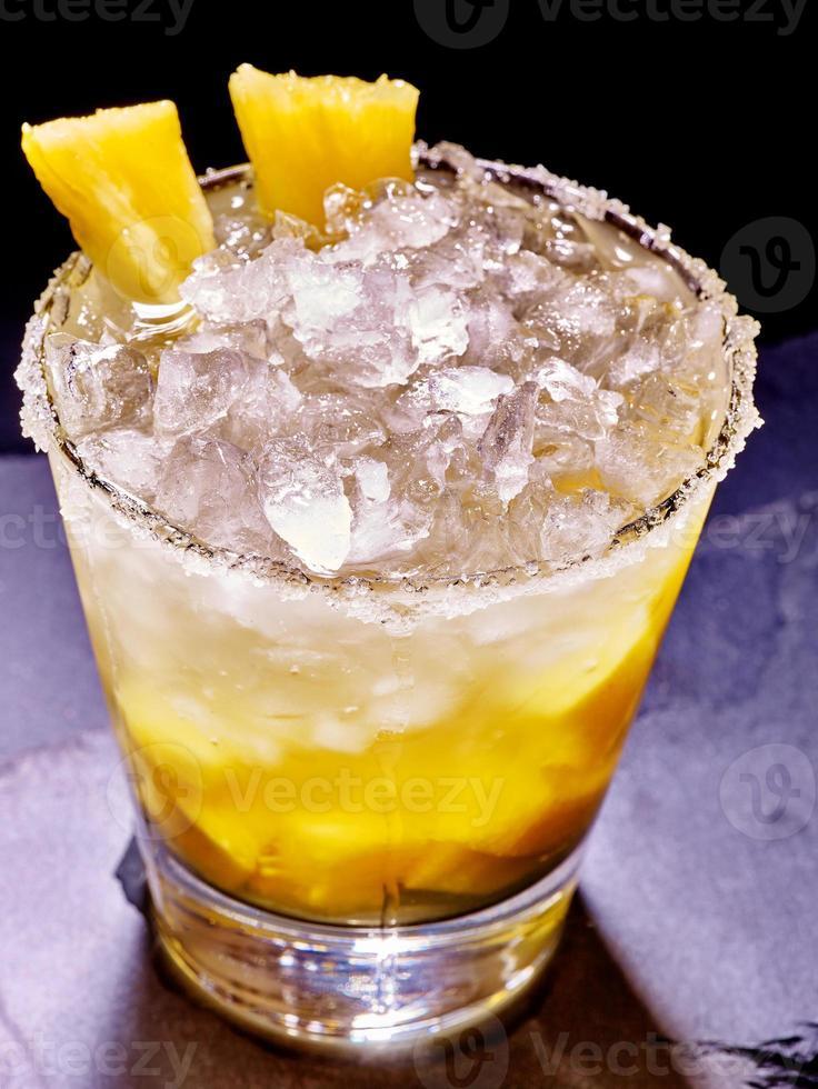 Cubo amarillo hielo de bebida fría con piña en la oscuridad foto