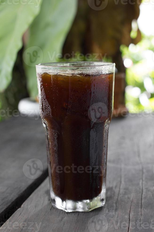 Ice black coffee on wooden table photo