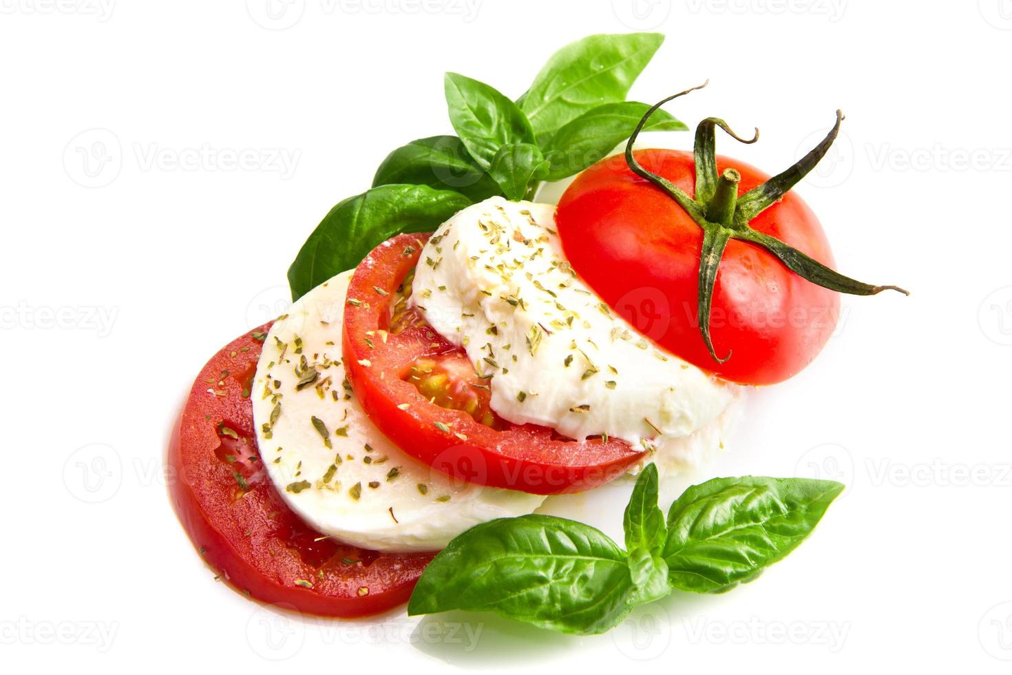 Tomato and mozzarella with basil leaves on white photo