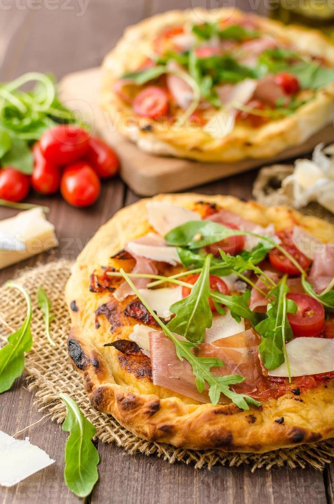 pizza italiana con queso parmesano, prosciutto y rúcula foto