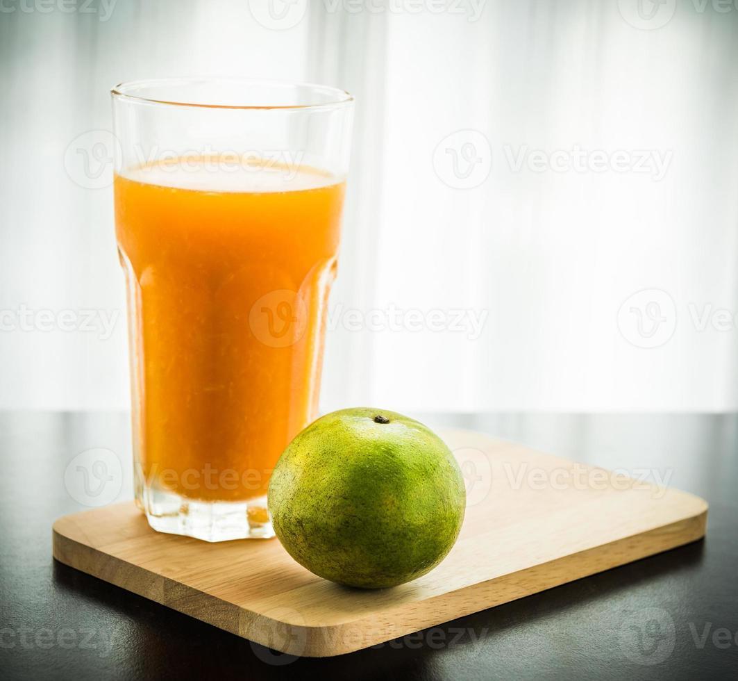 vaso de zumo de naranja recién exprimido con naranja foto